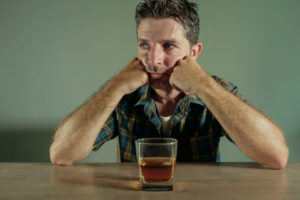 man wondering if his drinking habits are causing gum disease